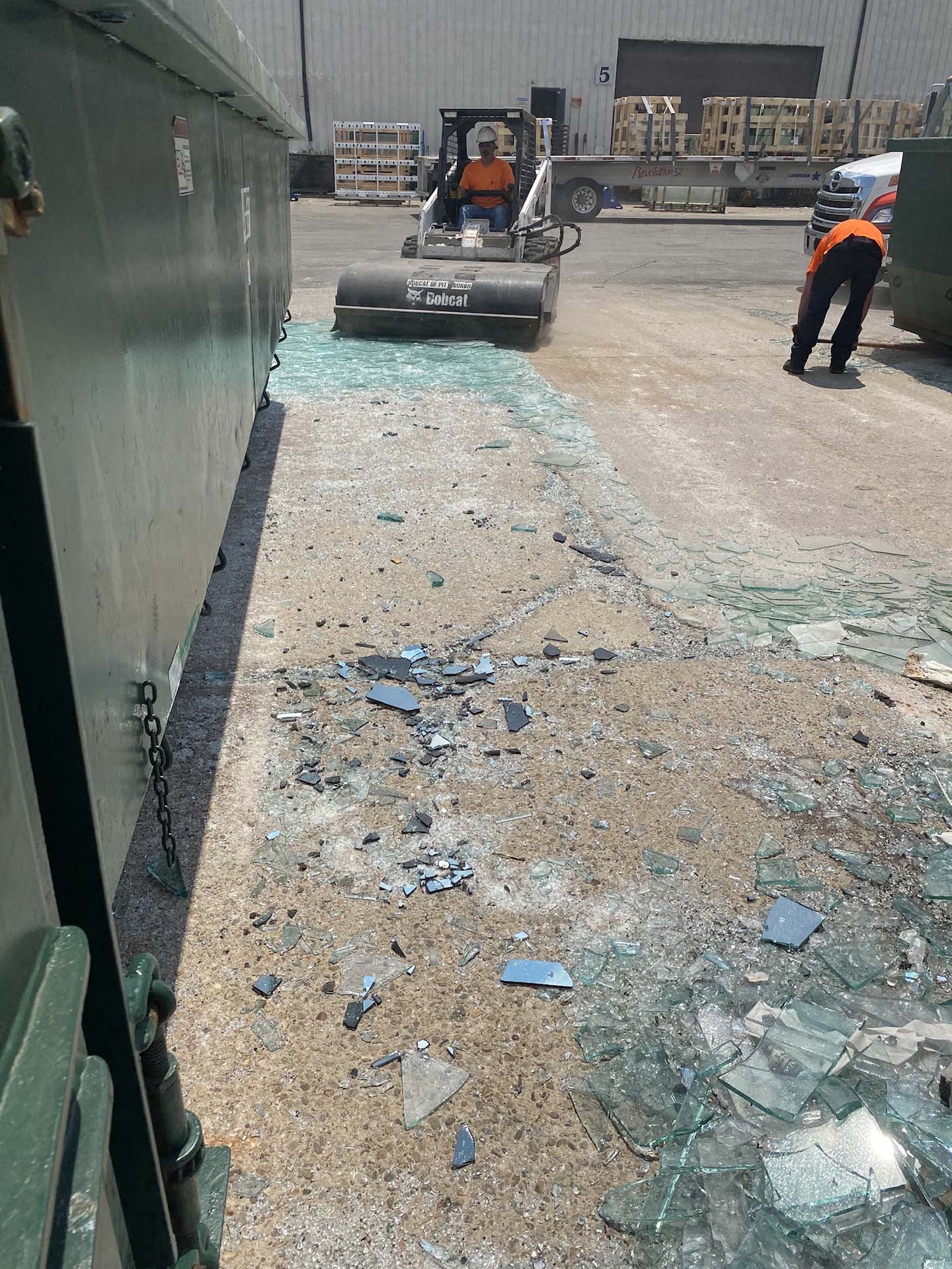 crew cleaning up broken glass on the ground