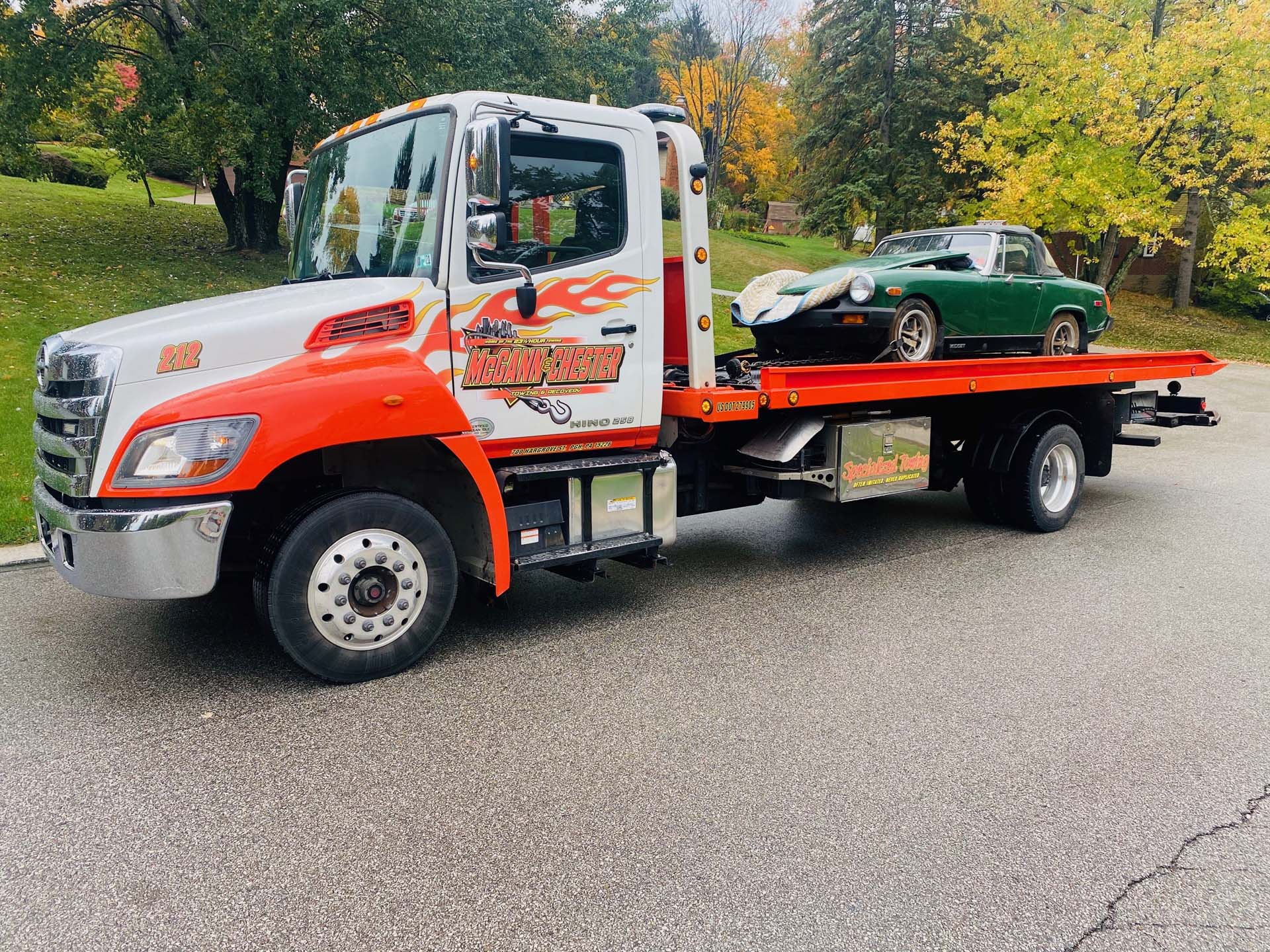 flatbed truck towing a car
